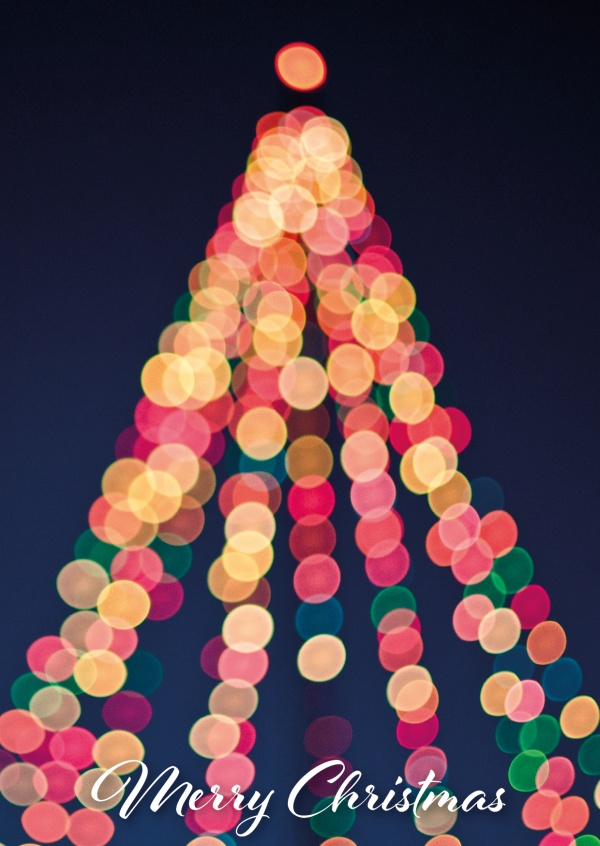 Greeting card with a photo of a colorful shining christmas tree