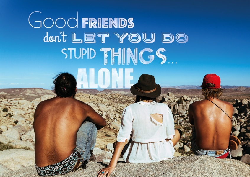 Three friends sitting togther on rocks in alone in the sun with the quote   good friends don`t let you do stupid things alone.