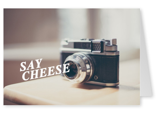 camera on desk with qoute say cheese