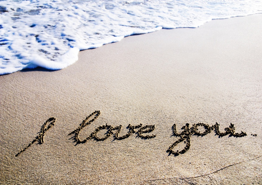 beach with waves and the message i love you written by hand in the sand