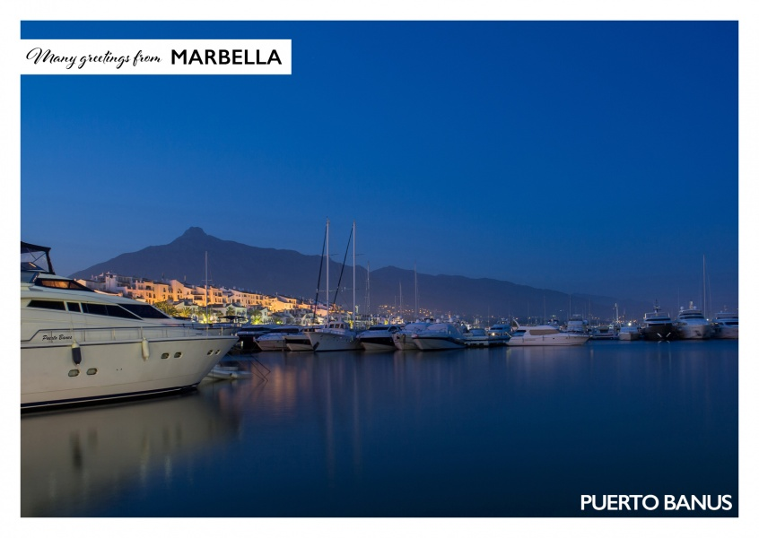 Photo of Puerto Banus in Marbella at night with mountains in the background