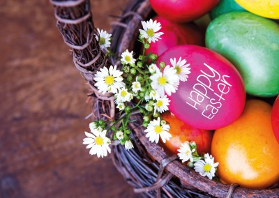 happy easter basket with Easter eggs and flowers