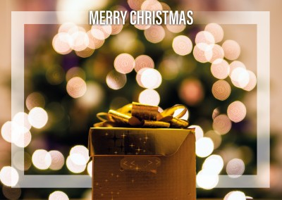 Christmas greeting card with a present in focus and lights in the backround