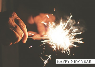 New years card with photo of a burning sparkler in the dark